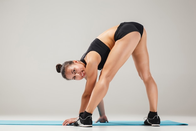 Mooi sportief meisje permanent in acrobaat pose of yoga asana