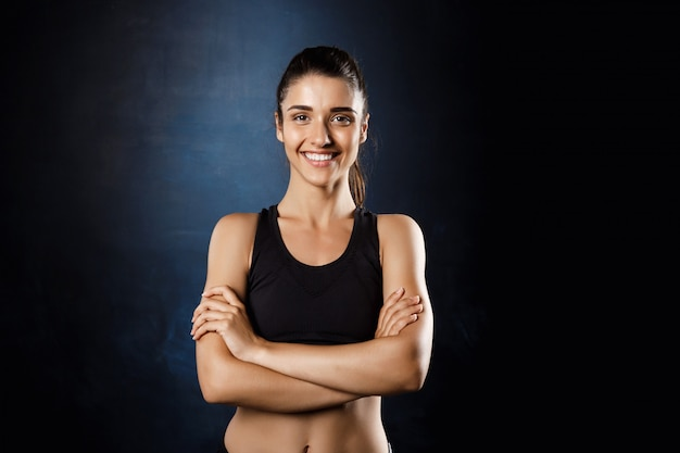 Mooi sportief meisje poseren met gekruiste armen over donkere muur.