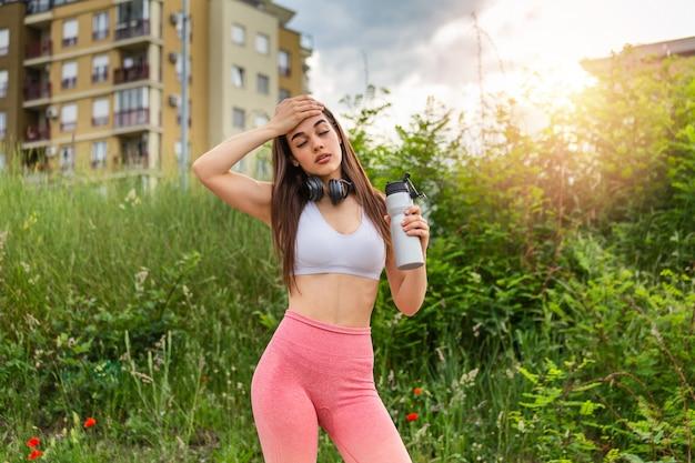 Mooi sportief vrouwen drinkwater terwijl het rusten van oefening.