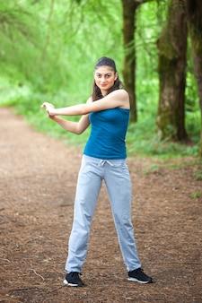 Mooi sportmeisje in het park houdt zich bezig met fitness, warming-up.