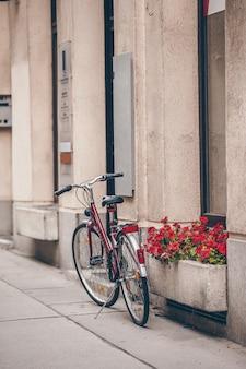 Mooi stadslandschap met een fiets dichtbij de oude muur met bloemen in wenen