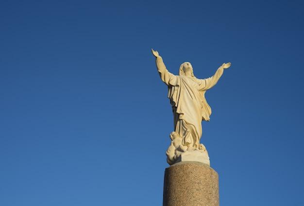 Mooi standbeeld van heilige vrouwen in rooms-katholieke kerk op blauwe hemelachtergrond