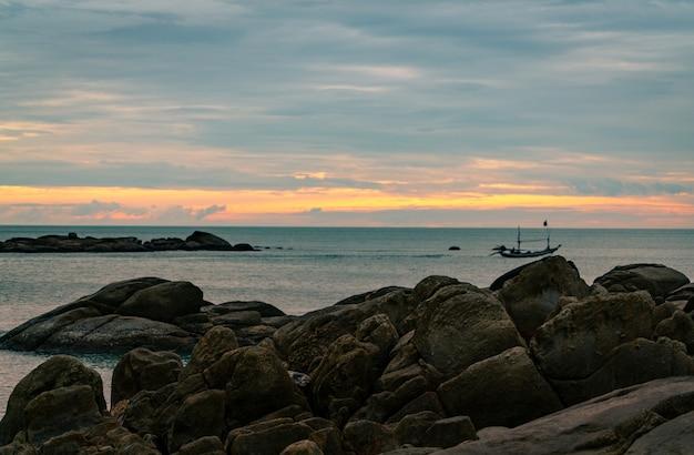 Mooi steenstrand in de ochtend met gouden zonsopganghemel. visser in lange staartboot met volksvisserijcultuur. vreedzame en rustige scène. kalme zee in de ochtend.