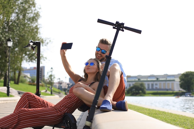 Mooi stel dat plezier heeft met het besturen van een elektrische scooter, een pauze neemt van het rijden, op de rivieroever zit, selfie neemt,