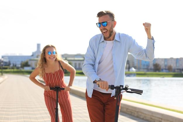 Mooi stel dat plezier heeft met het besturen van een elektrische scooter langs de stadspromenade.