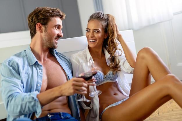 Mooi stel drinkt wijn, praat en lacht terwijl ze thuis tijd doorbrengen