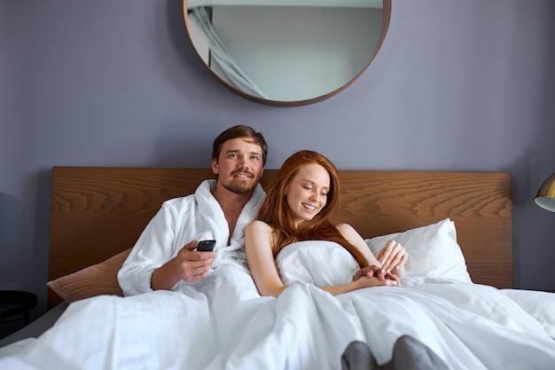 Mooi stel kijkt tv op bed, rust in het weekend in hotel