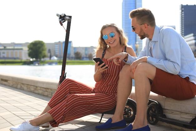 Mooi stel op vakantie dat plezier heeft met het besturen van een elektrische scooter, een pauze neemt van het rijden, zittend op de rivieroever.