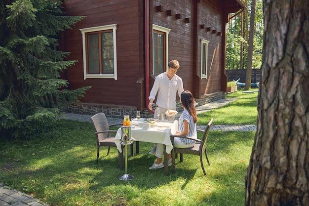 Mooi stel terwijl ze ontspannen in de groene tuin van hun moderne luxe huis