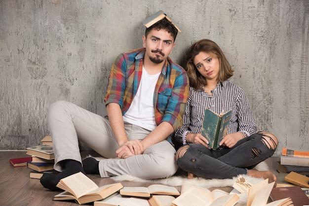 Mooi stel zittend op de vloer met veel boeken