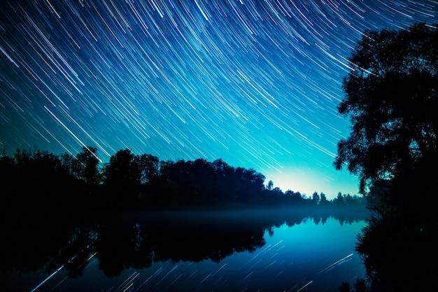 Mooi sterrenspoorbeeld tijdens de nacht over rivier