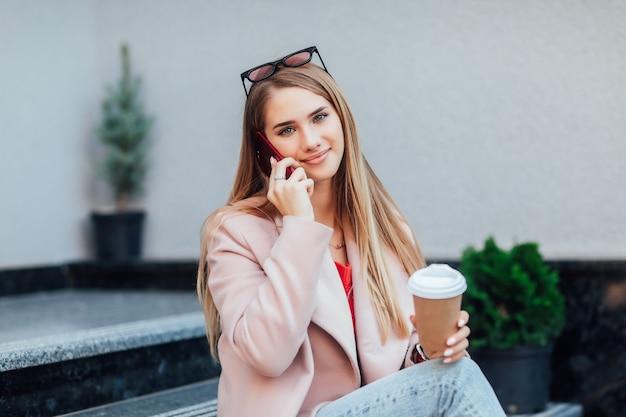 Mooi stijlvol meisje dat op straat zit, koffie op haar handen houdt en buiten poseert. kleding. rust tijd.