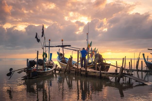 Mooi strand met vissersboot tijdens zonsopgang op vissersdorp