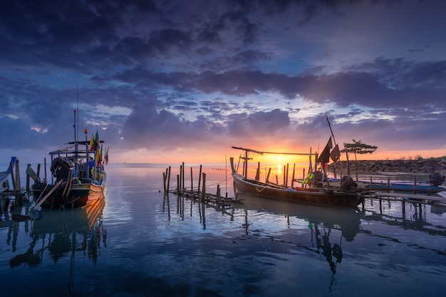 Mooi strand met vissersboot tijdens zonsopgang.