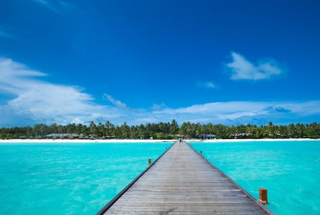 Mooi strand met wit zand. oceaan, blauwe lucht met wolken. zonnige dag. maldiven tropisch landschap