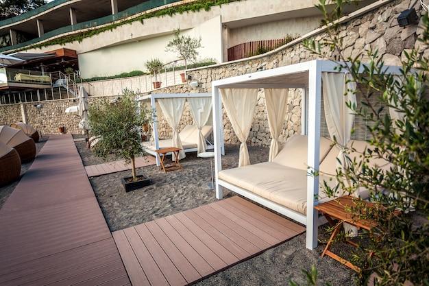Mooi strand met witte houten tenten met ligbedden bij luxe hotel