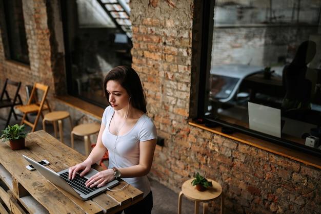 Mooi studentenmeisje die laptop en oortelefoons met behulp van terwijl status. bakstenen muur op de achtergrond.