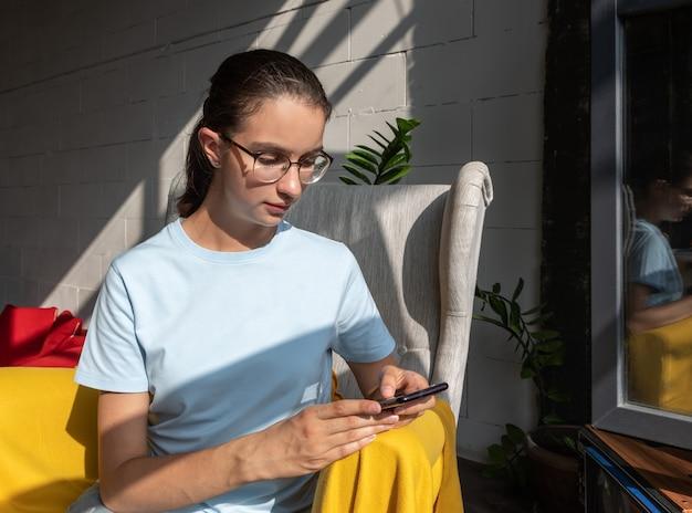 Mooi studentenmeisje met behulp van mobiele telefoon, sms, bericht, internet zoeken, café-applicaties, hard licht, diagonale schaduwen, verticaal frame. bedrijfsconcept. freelance concept