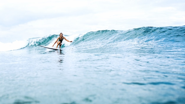 Mooi surfermeisje die op een raad berijden