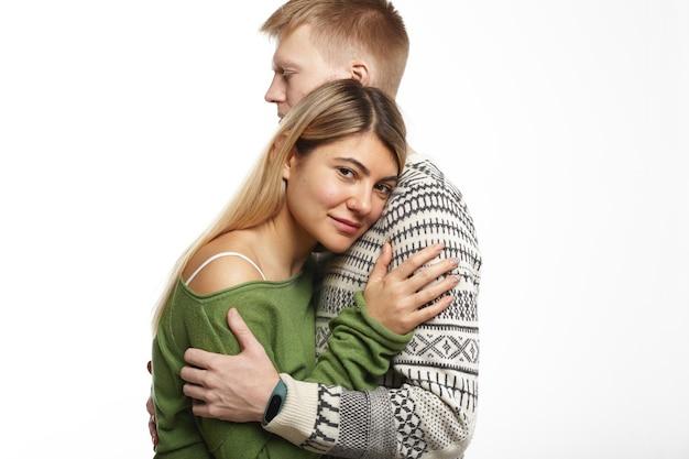 Mooi teder jong europees koppel knuffelen: knappe bebaarde man die zachtjes zijn aantrekkelijke vriendin omhelst die haar hoofd op zijn borst legt en glimlacht