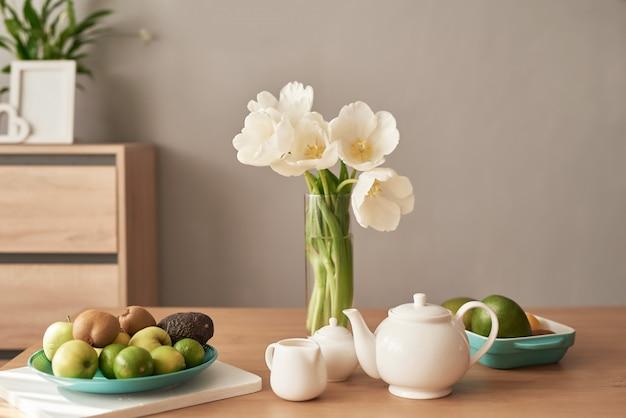 Mooi theeservies op houten tafel. home interieur, boeket bloemen in vaas, tafel met set van theepot.