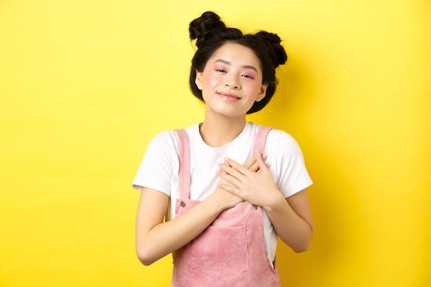 Mooi tiener aziatisch meisje verliefd, hand in hand op hart en glimlachend aangeraakt, kijkend met genegenheid, staande op geel.