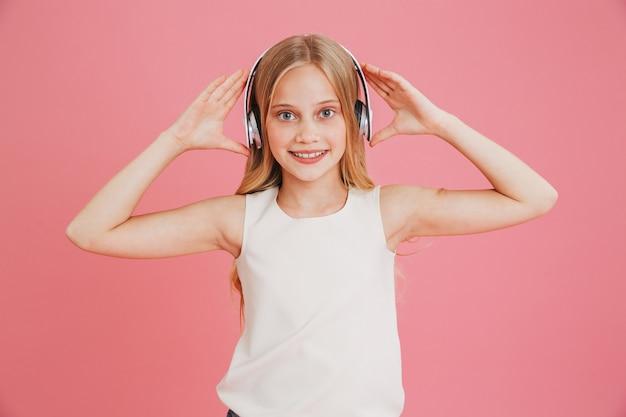 Mooi tienermeisje 8-10 in vrijetijdskleding, luisteren naar muziek en draadloze koptelefoon aan het hoofd, geïsoleerd op roze achtergrond aan te raken