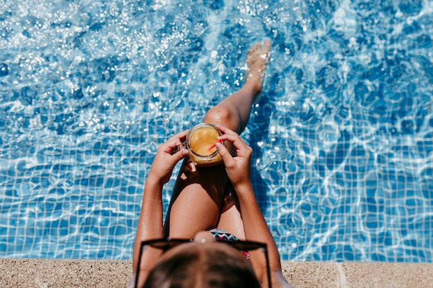 Mooi tienermeisje bij de pool die gezond jus d'orange drinkt en pret heeft in openlucht. zomer en levensstijl concept. bovenaanzicht