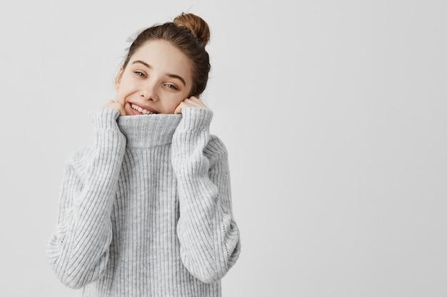 Mooi tienermeisje dat haar hals in kraag van wollen sweater met brede glimlach verbergt. vrouwelijk model poseren dragen koele warme outfit buigen hoofd naar kant. vreugde en geluk concept
