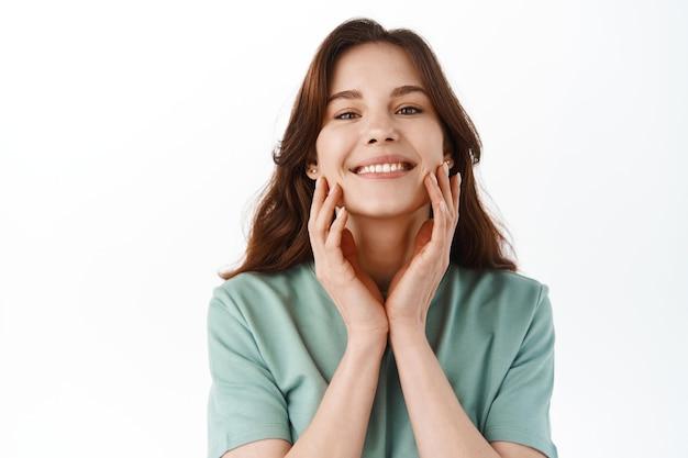 Mooi tienermeisje dat haar perfecte schone gezicht aanraakt en tevreden glimlacht, cosmetica gebruikt voor een betere hydratatie van het gezicht en een voedend effect, staande over een witte muur