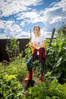 Mooi tienermeisje dat in de tuin werkt op een zonnige dag