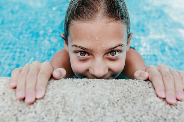 Mooi tienermeisje dat in een pool drijft en de camera bekijkt. plezier en zomer levensstijl