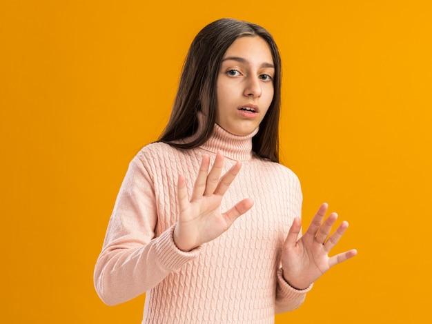 Mooi tienermeisje dat naar de voorkant kijkt en een weigeringsgebaar doet met open mond geïsoleerd op een oranje muur