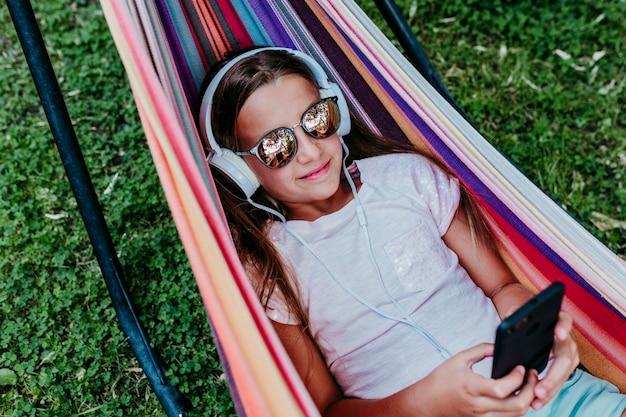 Mooi tienermeisje dat op kleurrijke hangmat bij de tuin ligt. luisteren naar muziek op mobiele telefoon en headset en glimlachen. ontspannen en plezier buitenshuis