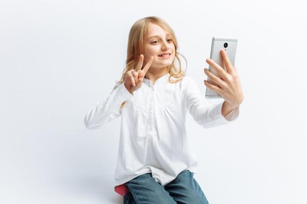 Mooi tienermeisje dat selfie op telefoon doet