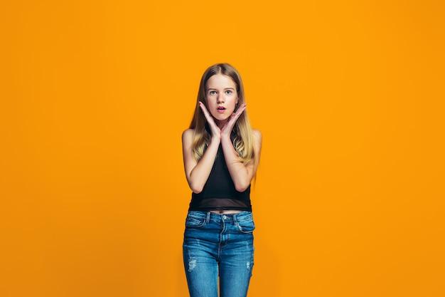 Mooi tienermeisje dat verrast kijkt dat op sinaasappel wordt geïsoleerd