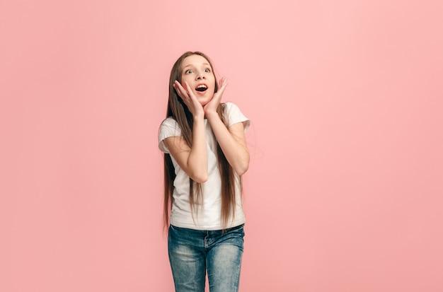 Mooi tienermeisje dat verrast kijkt geïsoleerd op roze