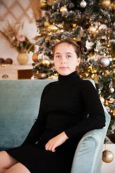 Mooi tienermeisje dichtbij kerstboom met giften.