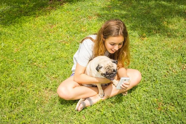 Mooi tienermeisje die op een grappige video op een smartphone met haar hond in een de zomerpark letten