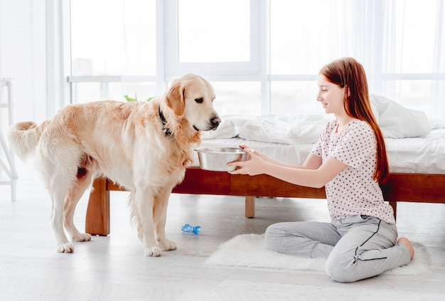 Mooi tienermeisje geeft 's ochtends eten aan golden retriever-hond in de slaapkamer. kid voedert huisdier hondje in de kamer met zonlicht. vriendelijke relaties tussen mens en dier
