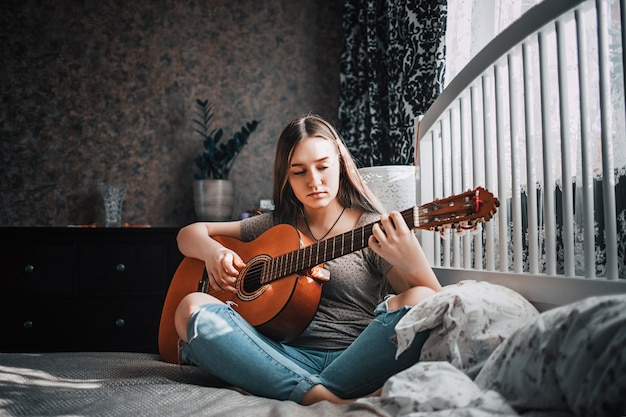 Mooi tienermeisje gitaarspelen in haar slaapkamer.