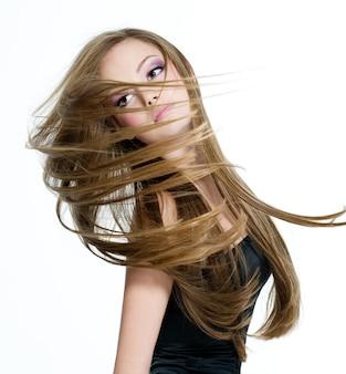 Mooi tienermeisje hoofd met lang haar schudden op hwite ruimte