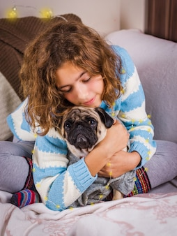 Mooi tienermeisje knuffels een pug hond met liefde. krullend meisje in een gebreide trui houdt een mopshond.