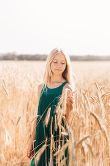 Mooi tienermeisje met lang wit haar dat op een zonnige dag door een tarweveld loopt