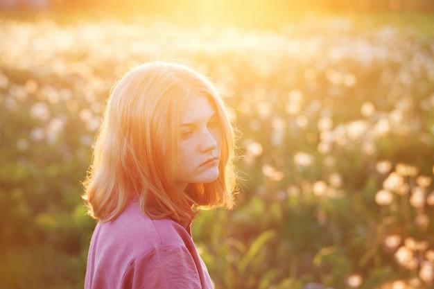 Mooi tienermeisje op achtergrondpaardebloemenweide bij zonsondergang
