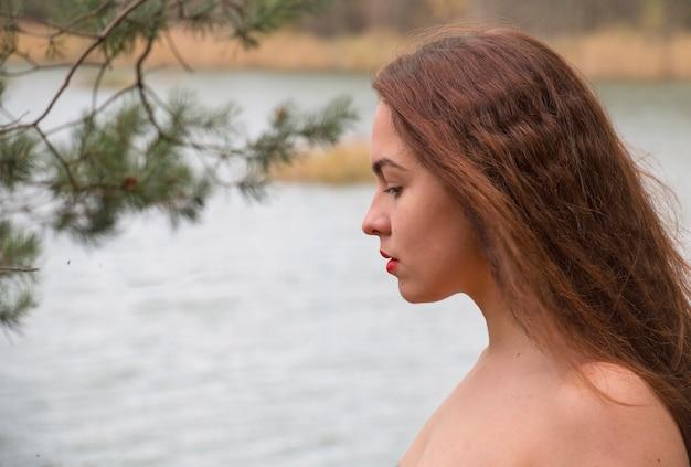 Mooi tienermeisje op de achtergrond van de rivier at, kijkend in de verte