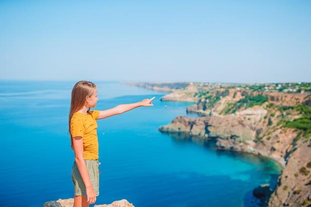 Mooi tienermeisje op de rand van de klif genieten van het uitzicht op de bergtop