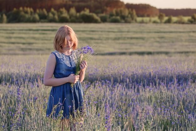 Mooi tienermeisje op de zomergebied met korenbloem