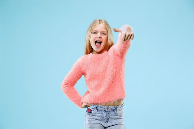 Mooi tienermeisje op zoek verrast geïsoleerd op blauw