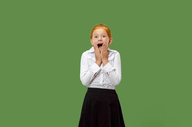 Mooi tienermeisje op zoek verrast geïsoleerd op groen